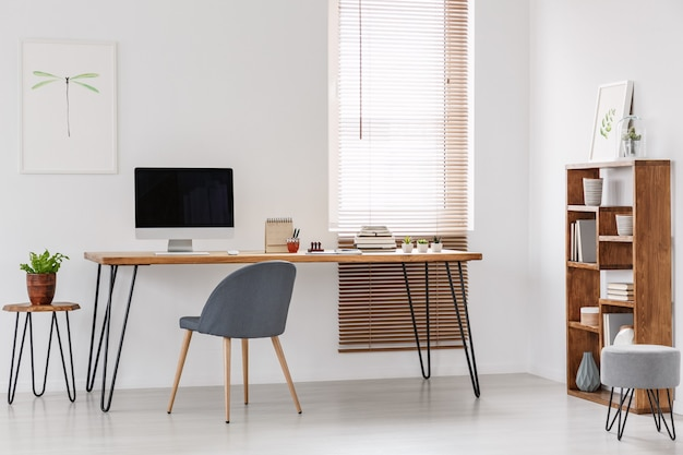 Natural and bright office of a start-up company with wooden furniture, desktop computer and gray chair at the desk. real photo