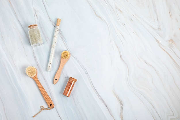 Natural bristle brushes, bath salt and clay masks in glass jars on white marble background. spa, self care and wellness concept. flat lay, top view