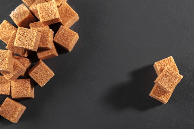 Natural brown sugar cubes on rough black