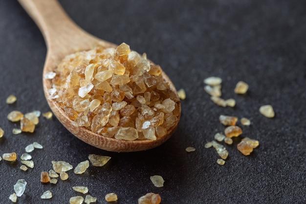 黒い花崗岩のテーブルの上に木のスプーンのナチュラルブラウンの砂糖か漂白剤の砂糖。