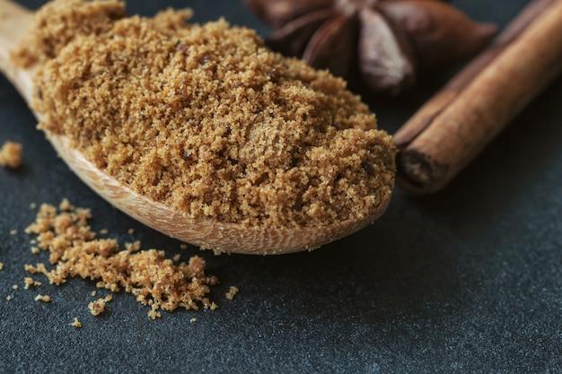 ナチュラルブラウンの砂糖または木のスプーンとシナモンスティックとアニスの未精製砂糖。