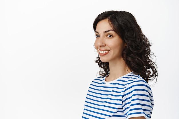 ピアスの鼻と巻き毛の髪型を持つ自然なブルネットの少女、白の空きスペースを脇に見て、縞模様のtシャツを着ています