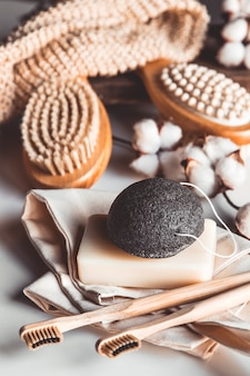 Natural brushes made of wood and soap on the background of concrete, bamboo toothbrushes and body brush, handmade soap with loofah, eco-friendly lifestyle concept and zero waste, copy space
