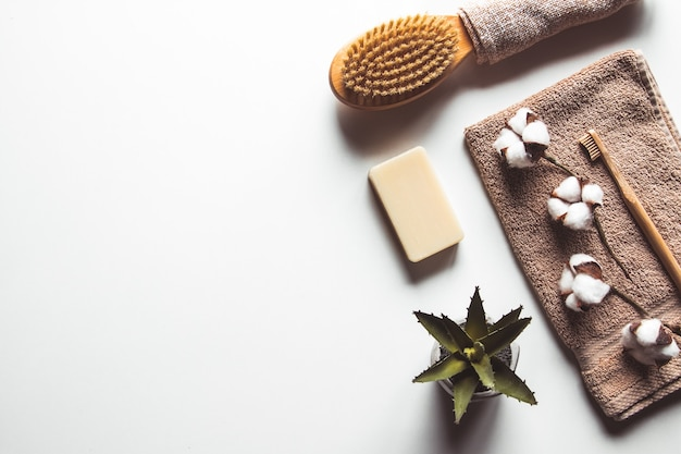Natural brushes made of wood and soap on the background of concrete, bamboo toothbrushes and body brush, handmade soap with loofah