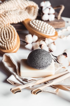 Natural brushes made of wood and soap on the of concrete, bamboo toothbrushes and body brush