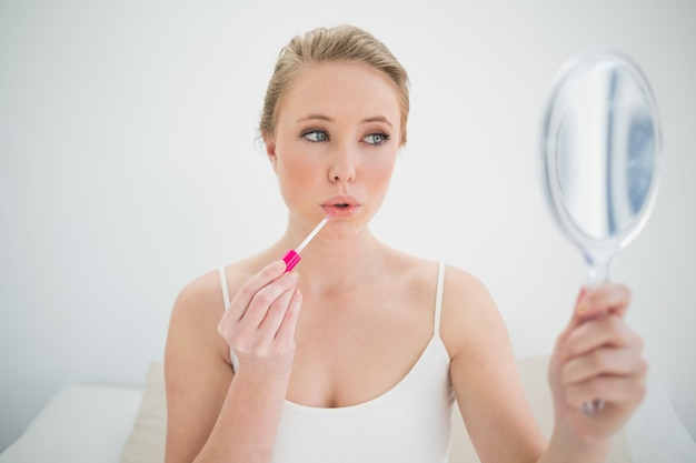 Natural calm blonde holding mirror and applying lip gloss