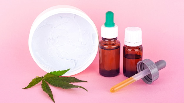 Натуральная косметика из конопли, органический крем для тела и рук из экстракта марихуаны на розовом фоне красоты.
