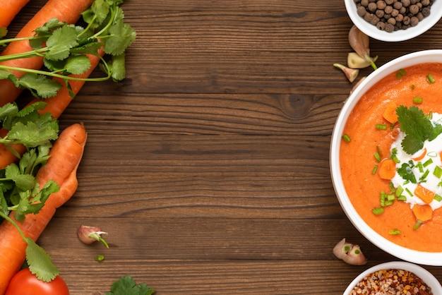 Натуральный морковный суп с зеленью на завтрак. на деревянном столе.