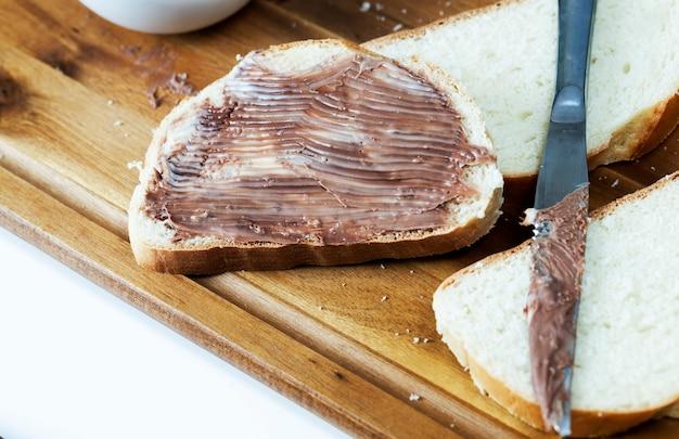 朝食時にココアを添えたナチュラルチョコレートペースト、スライスした白パンにチョコレートバターを塗ったもの、おいしいチョコレートバターと白パン