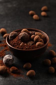 Natural chocolate truffles in decorative dishes, dark background, gloomy mood