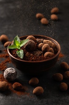 Natural chocolate truffles with mint in decorative dishes, dark background, dark mood
