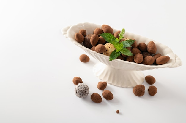 Natural chocolate truffles with mint in decorative dishes, white background