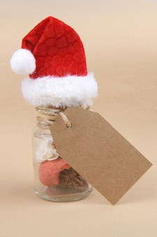 Natural christmas gift, a glass jars with dried herbs for aromatherapy wearing santa hat with empty rectungolar tag on craft paper backrgound