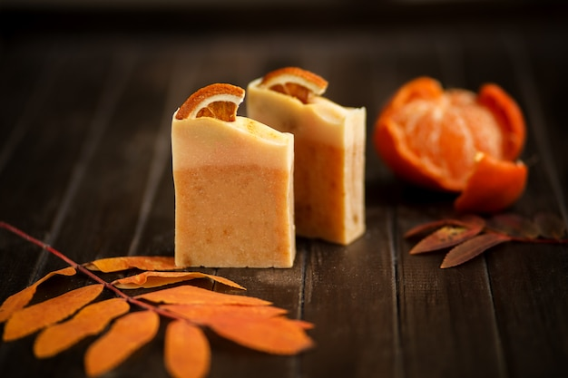 Natural citrus soap against autumn leaves and wooden background, close up, side view, organic cosmetics concept