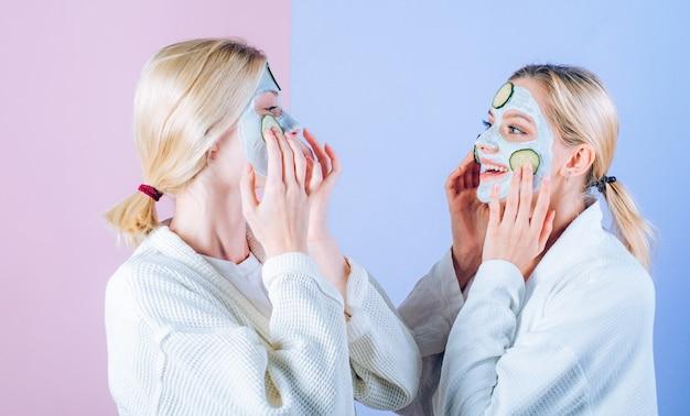 천연 클레이 페이셜 마스크. 여자 친구, 자매 또는 엄마와 딸이 클레이 페이셜 마스크를 만들고 있습니다. 안티에이징 마스크. 아름다워지세요. 모든 연령대의 피부 관리. 오이 스킨 마스크를 즐기는 여성.