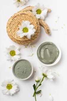 흰색 배경에 꽃으로 건조하고 젖은 천연 점토 마스크
