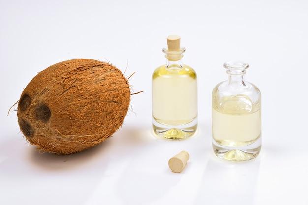 Натуральное кокосовое масло в бутылках на белой поверхности