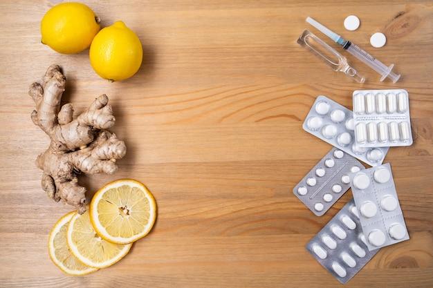自然な風邪やインフルエンザの家庭薬と合成の丸薬や薬、上面図。ハニーグラスポット、ジンジャー、ニンニク、レモン。免疫刺激とウイルス保護のための天然成分