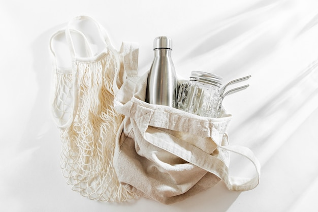 Natural color eco bag with reusable metal water bottle, glass jar and straw. zero waste.