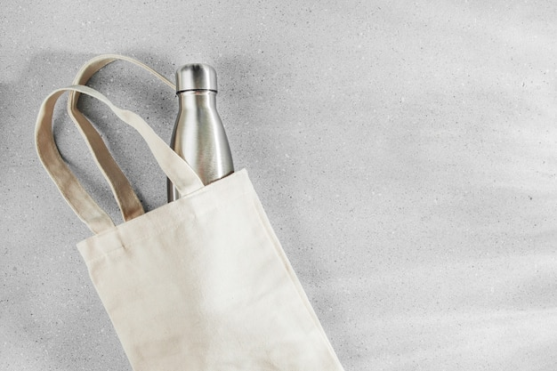 Эко-сумка натурального цвета с многоразовой металлической бутылкой для воды. концепция нулевых отходов. без пластика. плоская планировка, вид сверху