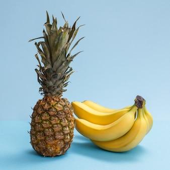 トロピカルフルーツを使った自然な組成。青い背景に新鮮なパイナップルとバナナ。