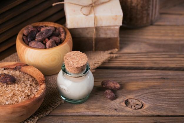 소박한 나무 배경에 천연 화장품 카카오 버터, 바다 소금, 코코아 콩을 넣은 천연 수제 비누. 건강한 피부 관리. 스파 개념입니다.