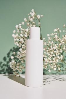 Бутылка натурального косметического крема на зеленом фоне с растением