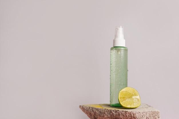 Натуральная косметическая зеленая бутылка с лаймом на основе цитрусовых масел на камне на серой сцене