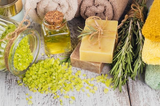 素朴な木製の背景にローズマリーと天然化粧品オイルと天然手作り石鹸。健康的なスキンケア。 spaのコンセプト。