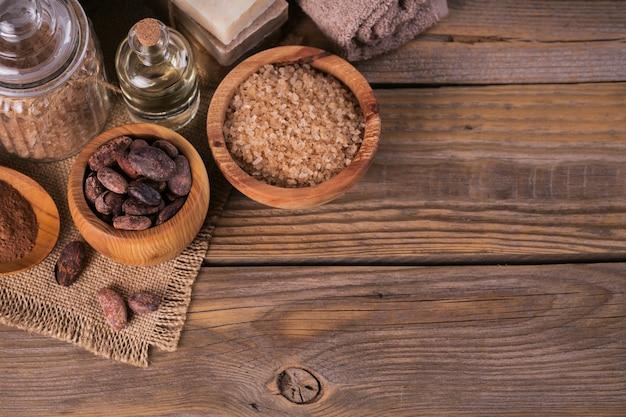 소박한 나무 배경에 코코아 콩을 넣은 천연 화장품 오일, 바다 소금, 천연 수제 비누. 건강한 피부 관리. 스파 개념입니다. 텍스트를 위한 공간이 있는 상위 뷰입니다.