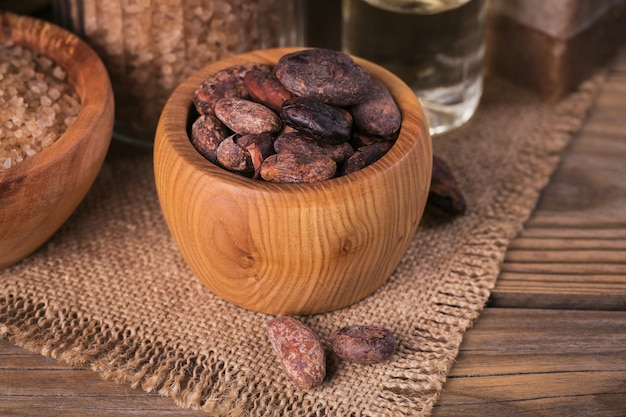 소박한 나무 배경에 코코아 콩을 넣은 천연 화장품 오일, 바다 소금, 천연 수제 비누. 건강한 피부 관리. 스파 개념입니다.