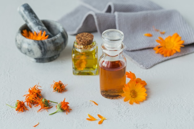 Natural cosmetic oil, tincture or infusion and mortar with calendula flowers dry and fresh on a light. healthy skin care. aromatherapy, spa and wellness concept