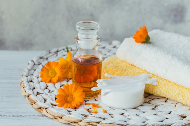 Натуральное косметическое масло, настойка или настой, ватный диск, палочки и полотенца с цветками календулы на светлой поверхности.
