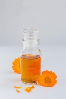 Натуральное косметическое масло, настойка или настой с цветками календулы на белом