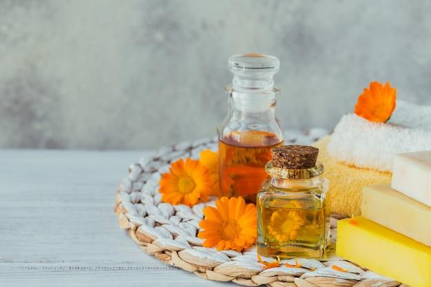 Натуральное косметическое масло, настой или настой и натуральное мыло ручной работы с цветками календулы.