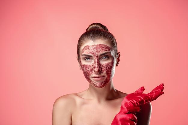 自然化粧品。赤い手袋で彼女の顔にイチゴのスクラブまたはマスクを持つ魅力的なブルネットの肖像画。
