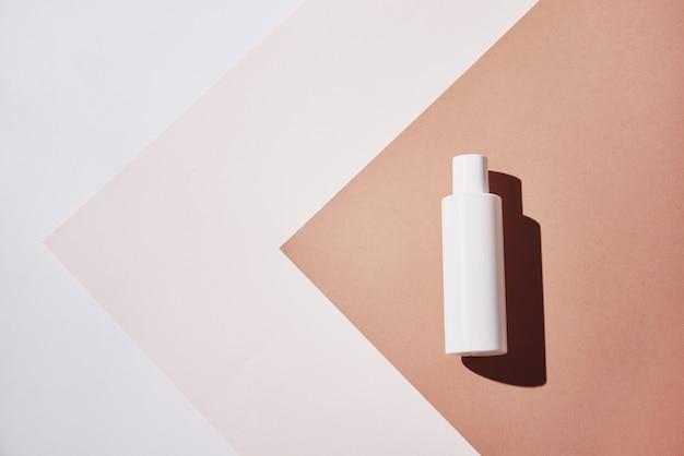 Белая бутылка натурального косметического продукта на пастельном фоне