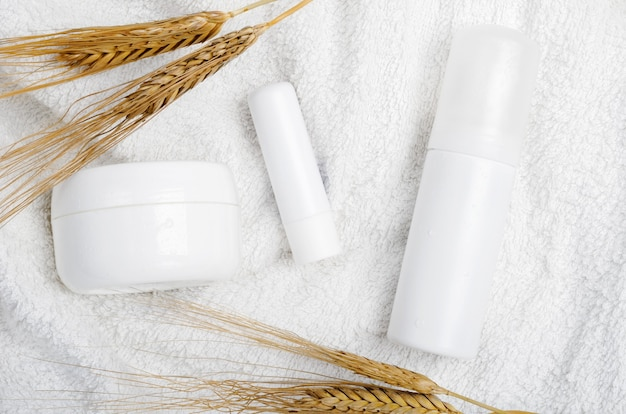 タオルの上の自然化粧品の容器