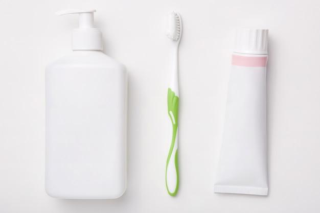 白い壁の歯磨き粉、歯ブラシ、クリームのボトルで分離された自然化粧品。美容コンセプト。衛生
