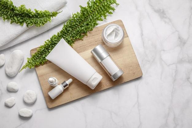 Натуральные косметические продукты с зелеными листьями на мраморном фоне. плоская планировка, вид сверху.