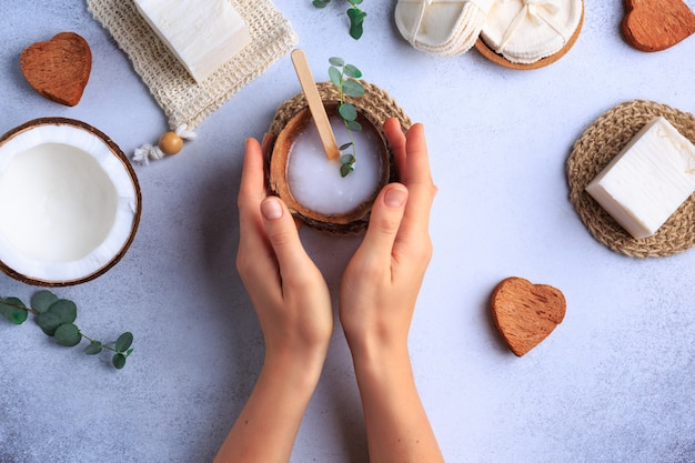 Natural cosmetic products setting with soaps and fresh herbs top view woman hands