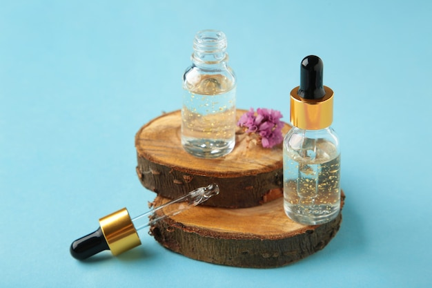 Natural cosmetic skincare bottle container with wood on blue surface with copy space for text