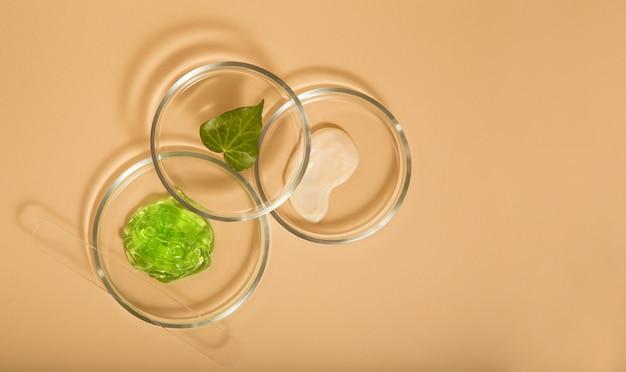 ベージュの背景にペトリ皿の自然化粧品スキンケア製品。アロエジェル、保湿クリーム