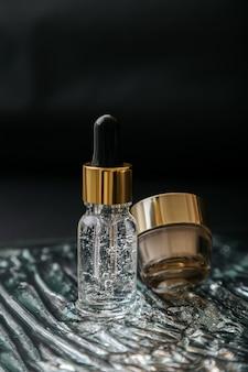 천연 코스메틱 스킨케어 세럼 유리병에는 액체 콜라겐 히알루론산과 보습 크림 병이 물 젤 질감의 어두운 표면에 있습니다. 럭셔리 골드 뷰티 유수분 밸런스 스킨 화장품.
