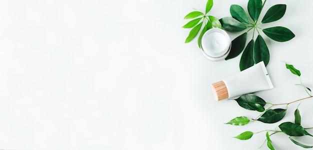 自然化粧品と緑の葉。化粧品とフラットレイアウト構成。