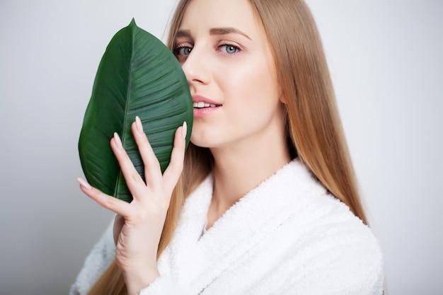 Натуральная косметика, красивое женское лицо в зеленых листьях.
