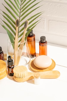自然化粧品、美容、エコリビングのコンセプト-木製の歯ブラシ、顔のマッサージブラシ、スポンジ、ブラシ、白い背景の石鹸。