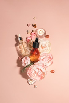 Natural cosmetics, bio serum and organic oils for skin care combined with flowers. natural skincare monochrome pastel concept