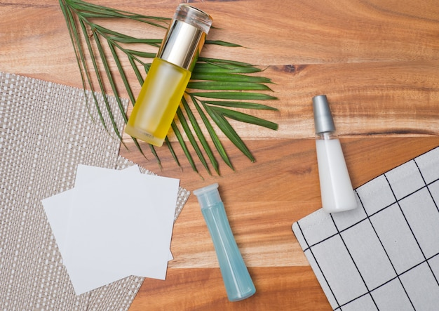 Natural cosmetics bottle containers on green leaf background with copy space