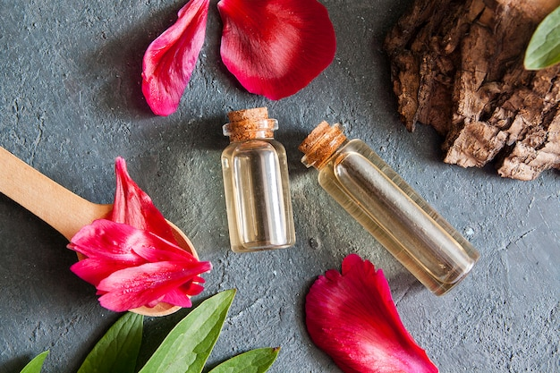 Natural cosmetics concept. bottles with essence, petals, flat lay wood on a dark background